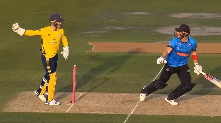 Hampshire wicket-keeper Lewis McManus runs out Sussex's Laurie Evans